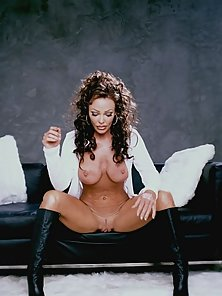 Brunette slightly matured busty chick posing seductively on the couch