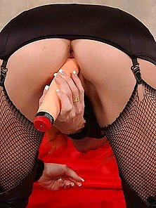 Redheaded masked slut in fishnets toying her pussy