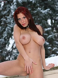 Stunning busty redhead melts snow with her hotness