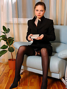 Brunette teen in black office wear posing and teasing indoors