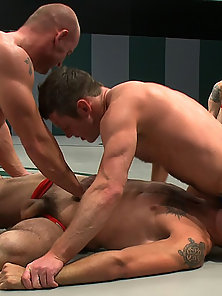 Four naked fighters fight in front of a screaming audience.