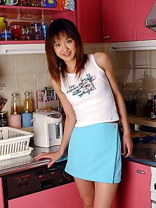 A horny Asian schoolgirl lifts up her blue skirt in the kitchen and shows off a little bit of camelt