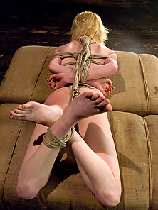 Shaved blond's pussy is tormented with tight crotch ropes.