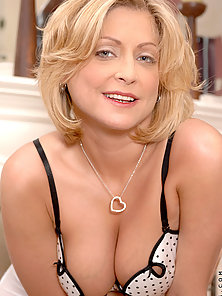 Seductive cougar shows off her huge tits while busy fingering her tight Anilos snatch